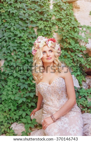 beautiful young woman in love in the park a wreath on his head, holding flowers in their hands He looks to the top summer - stock photo