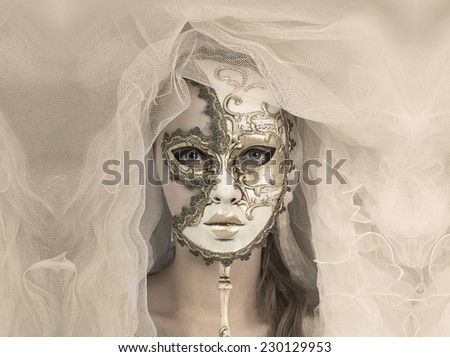 Beautiful young woman in mysterious golden Venetian mask.  - stock photo