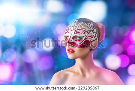 Beautiful young woman in mysterious venetian carnival mask - stock photo