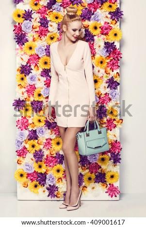 Beautiful young woman in nice dress, handbag  posing on colorful wall of flowers. Fashion spring photo, nice hair - stock photo