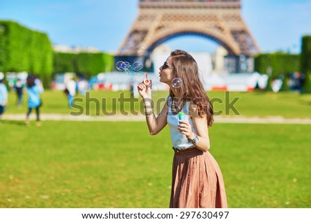 Beautiful young woman in Paris blowing bubbles near the Eiffel tower on a summer day - stock photo