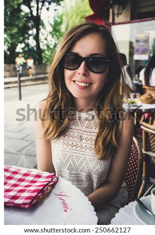 Beautiful young woman in Paris on holidays in France drinking coffee in Parisienne cafe on Champs-Elysees, Paris, France - stock photo