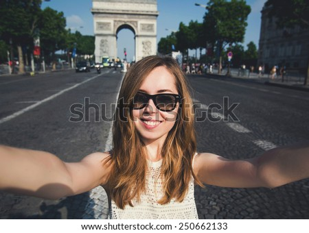 Beautiful young woman in Paris on holidays in France making selfie photo in front of Arc de Triomphe while walking on Champs-Elysees, Paris, France - stock photo