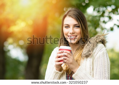 Beautiful young woman in park in autumn smiling holding cup of takeaway coffee. Happy blonde teenage girl outdoors in fall wearing beige sweater. Retouched, horizontal, vibrant colors. - stock photo