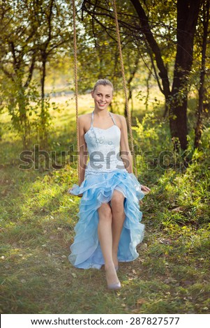 Beautiful young woman in prom dress sitting on swing on green summer outdoors - stock photo