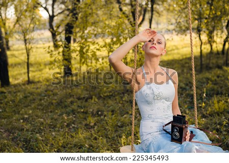 Beautiful young woman in prom or cocktail dress sitting on swings with retro photo camera on green summer or autumn outdoors copyspace background - stock photo