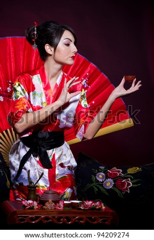 Beautiful young woman in red  Asian costume arranging Japanese tea ceremony - stock photo