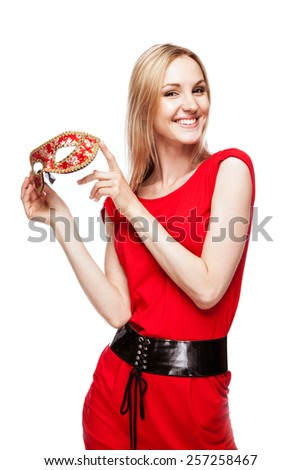 Beautiful young woman in red dress and carnival mask - stock photo
