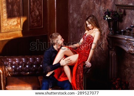 Beautiful young woman in red dress is flirting with elegant husband in luxury bedroom. - stock photo