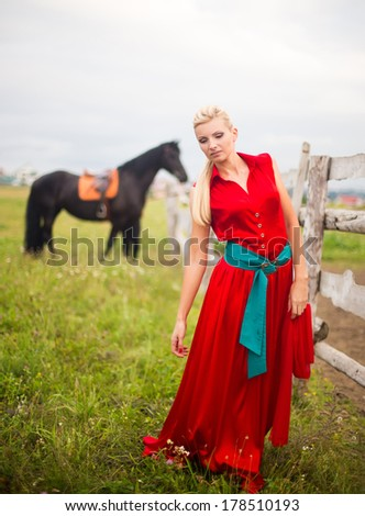 Beautiful young woman in red dress with a horse outdoor - stock photo