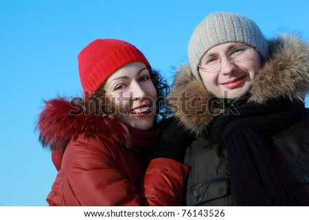 beautiful young woman in red jacket and man in glasses at winter outdoors - stock photo