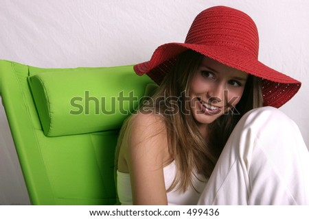 Beautiful young woman in red sun hat on green chair - stock photo