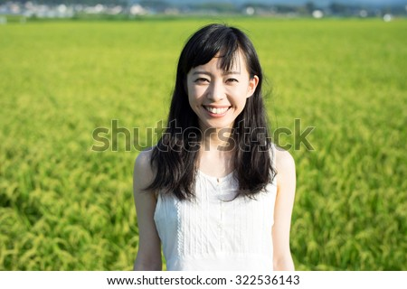 beautiful young woman in rice field - stock photo