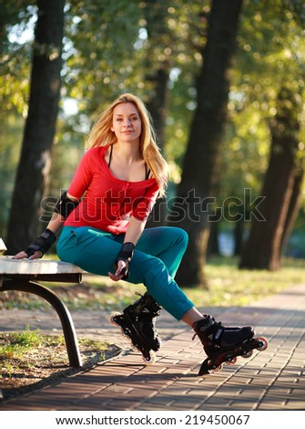 Beautiful young woman in roller skates sitting on park bench in summer sunny day - stock photo