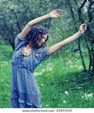 Beautiful young woman in romantic dress relaxing in garden - stock photo