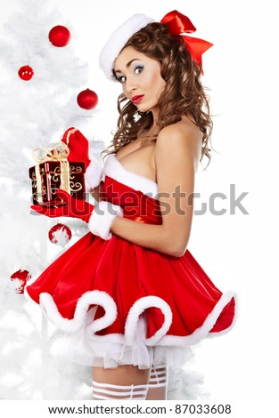 Beautiful young woman in Santa Claus clothes holding presents over Christmas background. - stock photo