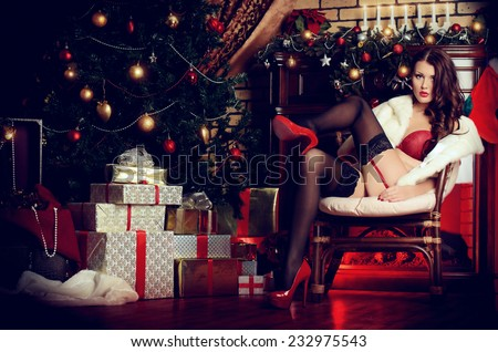 Beautiful young woman in sexual red lingerie and white fur coat posing in Christmas decorations. - stock photo