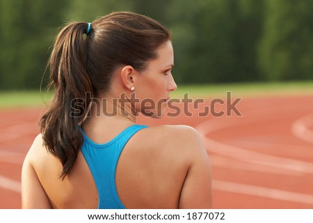 Beautiful Young Woman in Sports Bra Looking Over Shoulder - stock photo