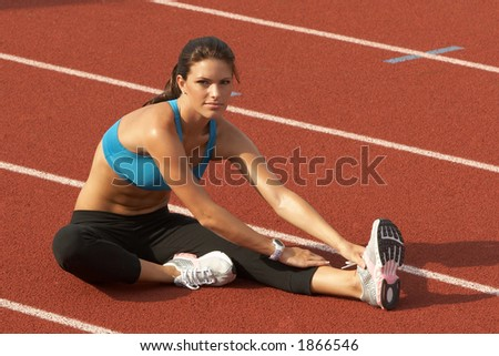 Beautiful Young Woman in Sports Bra Stretching Leg Muscles on Track - stock photo