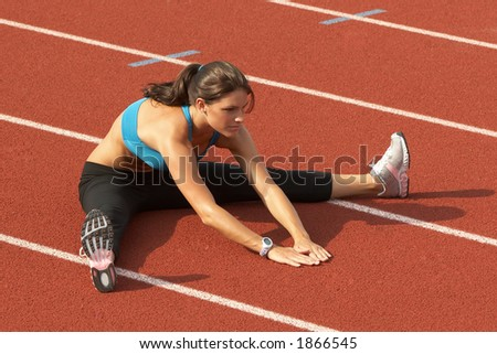 Beautiful Young Woman in Sports Bra Stretching Legs on Track - stock photo