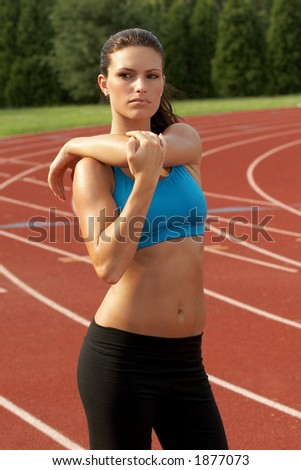 Beautiful Young Woman in Sports Bra Stretching Triceps Muscle - stock photo