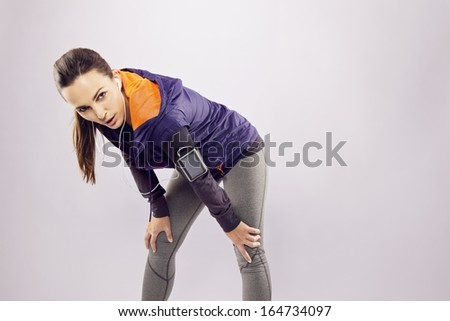 Beautiful young woman in sportswear looking tired after a run. Female runner resting with hands on knees over grey background - stock photo