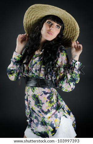 Beautiful young woman in straw hat posing on dark background - stock photo