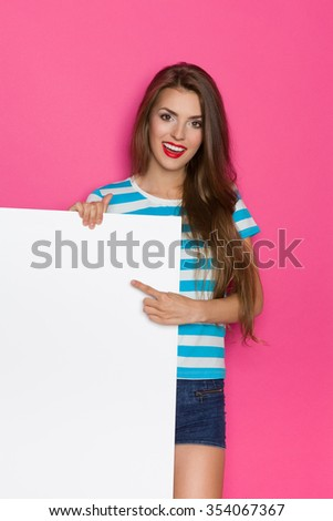Beautiful young woman in striped shirt and jeans shorts posing white placard and pointing. Three quarter length studio shot on pink background. - stock photo