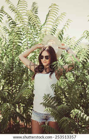 Beautiful young woman in stylish hat and jeans shorts posing. Hipster style. Summer time - stock photo