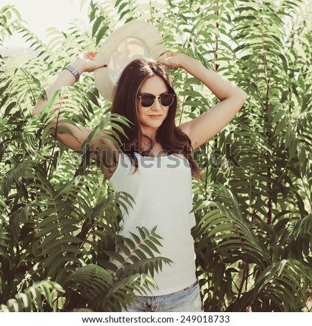 Beautiful young woman in stylish hat and jeans shorts posing. Hipster style. Summer time. Photo with instagram style filters - stock photo