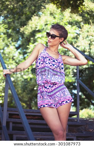 beautiful young woman in summer short jumpsuit and sunglasses outdoor shot - stock photo