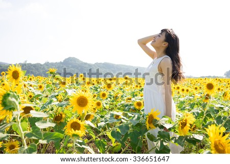 beautiful young woman in sunflower field - stock photo