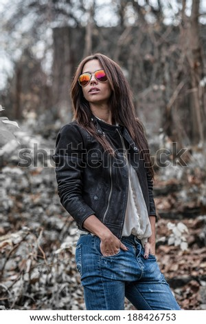 Beautiful young woman in sunglasses posing over nature background - stock photo
