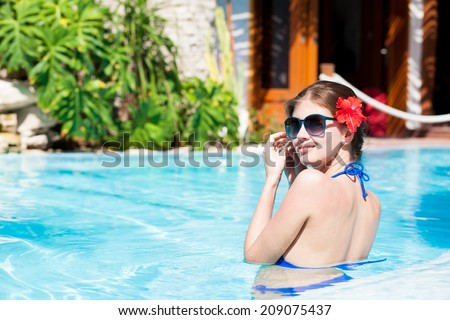 beautiful young woman in sunglasses with red flower in hair in a luxury swimming pool - stock photo