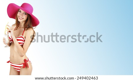 Beautiful young woman in swimsuit with cocktail on light blue background - stock photo