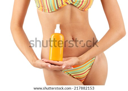 Beautiful young woman in swimsuit with sunscreen isolated on white - stock photo