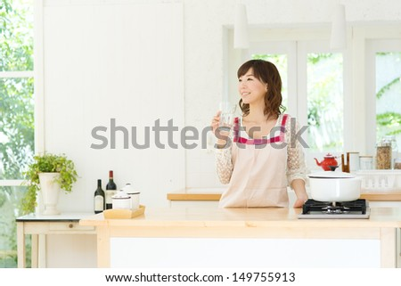 Beautiful young woman in the kitchen - stock photo