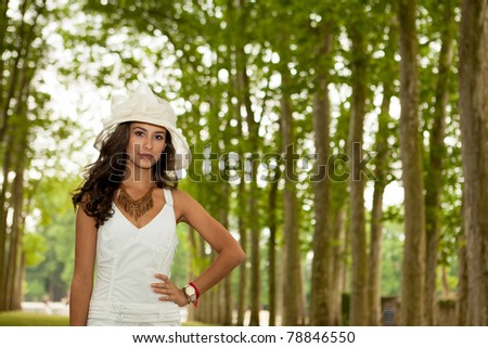 Beautiful young woman in the Parisian countryside along a tall row of trees. - stock photo