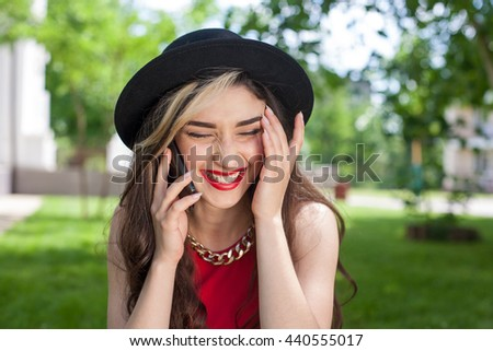 Beautiful young woman in the park, smiling, talking on mobile phone, laughing . Woman in black classical hat with red lips. Long hair. Technology and people concept - stock photo