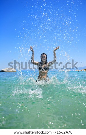 Beautiful young woman in the sea spashing water - stock photo
