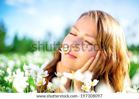 beautiful young woman in the summer park, lying on the grass with flowers - stock photo