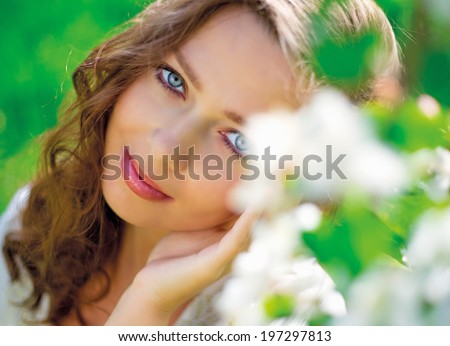 beautiful young woman in the summer park, near the apple tree with flowers   - stock photo