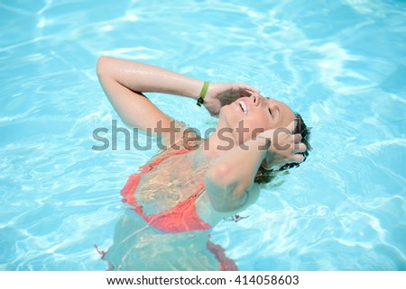 beautiful young woman in the swimming pool on a sunny summer day - stock photo