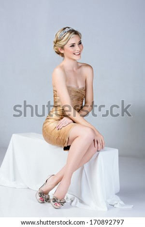 Beautiful young woman in tight gold mini dress sitting on studio background  - stock photo