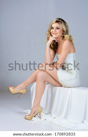 Beautiful young woman in tight white wedding dress sitting on studio background  - stock photo