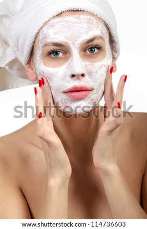 Beautiful young woman in towel doing cosmetic mask on her face - stock photo