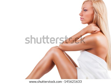 Beautiful young woman in towel sitting on the floor isolated on white background - stock photo