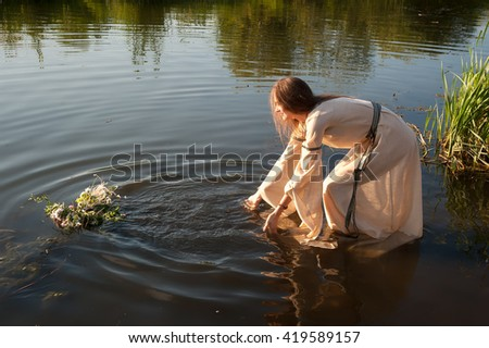Beautiful young woman in traditional dress puts wreath in water of lake. Russian traditional Ivan Kupala holiday celebration - stock photo