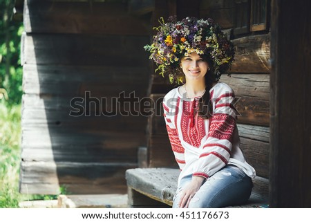 beautiful young woman in traditional Ukrainian costume and a large floral wreath sits on a bench near wooden house. - stock photo