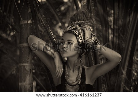 beautiful young woman in turban with jungle background. Black and white portrait - stock photo